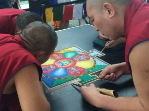 Tibetan Buddhist monks make a sand mandala